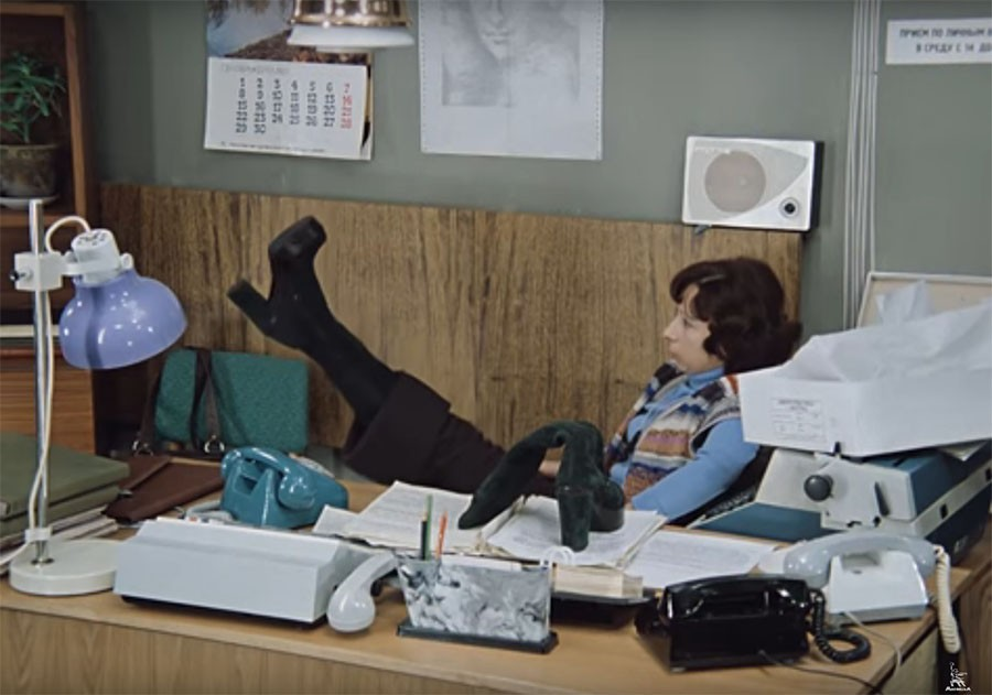 Кадр из фильма «Служебный роман». Героиня – секретарша Верочка – примеряет дефицитные импортные сапоги